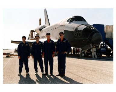 """KENNEDY SPACE CENTER, FLA. -- Four members of the STS-81 crew pose in front of the Space Shuttle orbiter Atlantis on Runway 33 of KSC?s Shuttle Landing Facility after the space plane touched down at 9:22:44 a.m. EST Jan. 22 to conclude the fifth Shuttle-Mir docking mission. The crew members are (from left): Mission Specialists John M. Grunsfeld and Peter J. K. """"Jeff"""" Wisoff ; Pilot Brent W. Jett, Jr.; and Mission Commander Michael A. Baker. Also returning on board Atlantis were Mission Specialist Marsha S. Ivins and John Blaha, who had been a member of the Mir 22 crew for four months. At main gear touchdown, the STS-81 mission duration was 10 days, 4 hours, 55 minutes. This was the 34th KSC landing in Shuttle history"""