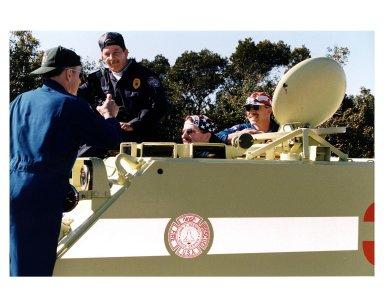"""STS-82 Mission Commander, far left, takes a photograph of his fellow crew members Pilot Scott J. """"Doc"""" Horowitz, at far right, and Mission Specialist Joseph R. """"Joe"""" Tanner while they are training in the M-113 armored personnel carrier. George Hoggard, a training officer with KSC Fire Services, looks on. The STS-82 crew is at KSC to participate in the Terminal Countdown Demonstration Test (TCDT), a dress rehearsal for launch. The 10-day flight, which will be the second Hubble Space Telescope servicing mission, is targeted for a Feb. 11 liftoff"""