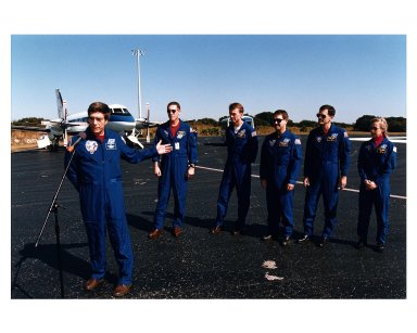 """Returning NASA astronaut and former Mir 22 crew member John E. Blaha (left), gestures towards his fellow STS-81 crew members during a press conference prior to their departure for Johnson Space Center Jan. 23 from the Skid Strip at Cape Canaveral Air Station. The crew arrived at KSC aboard the Space Shuttle Atlantis Jan. 22 to conclude the fifth Shuttle-Mir docking mission and return Blaha to Earth after four months in space. Behind Blaha from the left are Mission Commander Michael A. Baker; Pilot Brent W. Jett, and Mission Specialists John M. Grunsfeld, Peter J. K. """"Jeff"""" Wisoff and Marsha S. Ivins"""