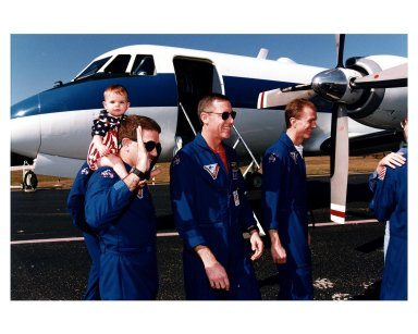 Members of the STS-81 crew prepare to depart for Johnson Space Center Jan. 23 from the Skid Strip at Cape Canaveral Air Station. The crew arrived at KSC aboard the Space Shuttle Atlantis Jan. 22 to conclude the fifth Shuttle-Mir docking mission and return U. S. astronaut John E. Blaha to Earth after four months in space as member of the Mir 22 crew. On the left is Mission Specialist John M. Grunsfeld, with his daughter, Sarah, on his back. Also pictured are Mission Commander Michael A. Baker (center); Pilot Brent W. Jett (second from right); and Blaha