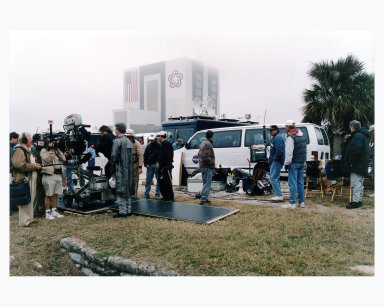 """With the Vehicle Assembly Building looming in the background, Warner Bros.' cast and crew are filming scenes for the movie """"Contact"""" at Kennedy Space Center's Launch Complex 39 Press Site on January 30. The screenplay for """"Contact"""" is based on the best-selling novel by the late astronomer Carl Sagan. The cast includes Jodie Foster, Matthew McConaughey, John Hurt, James Woods, Tom Skerritt, David Morse, William Fichtner, Rob Lowe and Angela Bassett. Described by Warner Bros. as a science fiction drama, """"Contact"""" will depict humankind's first encounter with evidence of extraterrestrial life"""