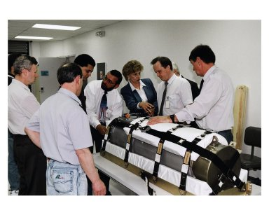 Representatives of RSC Energia in Russia and other onlookers in the SPACEHAB Payload Processing Facility examine an oxygen generator which the Space Shuttle Atlantis will carry to the Russian Mir Space Station on Mission STS-84. Sergei Romanov, second from right in the white shirt, is the spokesperson for generator manufacturer RSC Energia. The nearly 300-pound generator will be strapped down on the inside surface of a SPACEHAB Double Module for the trip to Mir. It will replace one of two Mir units that have been malfunctioning recently. The generator functions by electrolysis, which separates water into its oxygen and hydrogen components. The hydrogen is vented and the oxygen is used for breathing by the Mir crew. The generator is 4.2 feet in length and 1.4 feet in diameter. STS-84, which is planned to include a Mir crew exchange of astronaut C. Michael Foale for Jerry M. Linenger, is targeted for a May 15 liftoff. It will be the sixth Shuttle-Mir docking