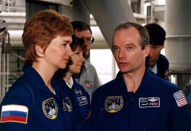 STS-84 Commander Charles J. Precourt, in right foreground, talks to fellow crew members, Mission Specialist Elena V. Kondakova, in left foreground, of the Russian Space Agency, and Pilot Eileen Marie Collins during Terminal Countdown Demonstration Test (TCDT) activities at Launch Pad 39A. In the background are NASA suit technician Al Rochford, at left, and astronaut Mario Runco Jr., who is assisting the STS-84 crew. STS-84 will be the sixth docking of the Space Shuttle with the Russian Space Station Mir. After docking, STS-84 Mission Specialist Michael C. Foale will transfer to the space station and become a member of the Mir 23 crew, replacing U.S. astronaut Jerry M. Linenger, who will return to Earth aboard Atlantis. Foale will live and work on Mir until mid-September when his replacement is expected to arrive on the STS-86 mission. STS-84 is targeted for a May 15 liftoff