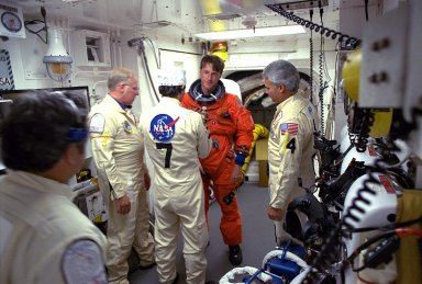 STS-84 Mission Specialist C. Michael Foale prepares to enter the Space Shuttle Atlantis at Launch Pad 39A with help from white room closeout crew members. The fourth Shuttle mission of 1997 will be the sixth docking of the Space Shuttle with the Russian Space Station Mir. The commander is Charles J. Precourt. The pilot is Eileen Marie Collins. The five mission specialists are C. Michael Foale, Carlos I. Noriega, Edward Tsang Lu, Jean-Francois Clervoy of the European Space Agency and Elena V. Kondakova of the Russian Space Agency. The planned nine-day mission will include the exchange of Foale for U.S. astronaut and Mir 23 crew member Jerry M. Linenger, who has been on Mir since Jan. 15. Linenger transferred to Mir during the last docking mission, STS-81; he will return to Earth on Atlantis. Foale is slated to remain on Mir for about four months until he is replaced in September by STS-86 Mission Specialist Wendy B. Lawrence. During the five days Atlantis is scheduled to be docked with the Mir, the STS-84 crew and the Mir 23 crew, including two Russian cosmonauts, Commander Vasily Tsibliev and Flight Engineer Alexander Lazutkin, will participate in joint experiments. The STS-84 mission also will involve the transfer of more than 7,300 pounds of water, logistics and science equipment to and from the Mir. Atlantis is carrying a nearly 300-pound oxygen generator to replace one of two Mir units which have experienced malfunctions. The oxygen it generates is used for breathing by the Mir crew