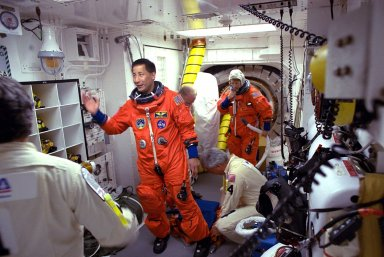 STS-84 Mission Specialist Edward T. Lu prepares to enter the Space Shuttle Atlantis at Launch Pad 39A with help from white room closeout crew members. The fourth Shuttle mission of 1997 will be the sixth docking of the Space Shuttle with the Russian Space Station Mir. The commander is Charles J. Precourt. The pilot is Eileen Marie Collins. The five mission specialists are C. Michael Foale, Carlos I. Noriega, Edward Tsang Lu, Jean-Francois Clervoy of the European Space Agency and Elena V. Kondakova of the Russian Space Agency. The planned nine-day mission will include the exchange of Foale for U.S. astronaut and Mir 23 crew member Jerry M. Linenger, who has been on Mir since Jan. 15. Linenger transferred to Mir during the last docking mission, STS-81; he will return to Earth on Atlantis. Foale is slated to remain on Mir for about four months until he is replaced in September by STS-86 Mission Specialist Wendy B. Lawrence. During the five days Atlantis is scheduled to be docked with the Mir, the STS-84 crew and the Mir 23 crew, including two Russian cosmonauts, Commander Vasily Tsibliev and Flight Engineer Alexander Lazutkin, will participate in joint experiments. The STS-84 mission also will involve the transfer of more than 7,300 pounds of water, logistics and science equipment to and from the Mir. Atlantis is carrying a nearly 300-pound oxygen generator to replace one of two Mir units which have experienced malfunctions. The oxygen it generates is used for breathing by the Mir crew