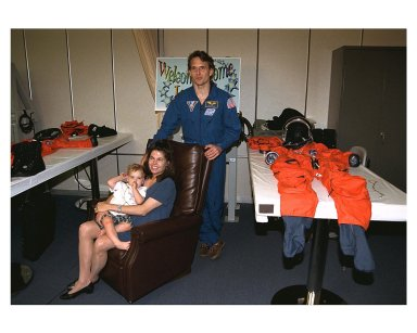 Astronaut and recent Mir 23 crew member Jerry M. Linenger, standing, reunites with his wife, Kathryn, and their 18-month-old son, John, in the astronaut suit-up room in the Operations and Checkout Building. Kathryn Linenger is expecting their second child next month. Linenger just returned to Earth after a four-month stay on the Russian Space Station Mir. He flew back on Atlantis with six other members of the STS-84 crew, who conducted the sixth Space Shuttle docking with the Mir. STS-84 Mission Specialist C. Michael Foale replaced Linenger on the Mir