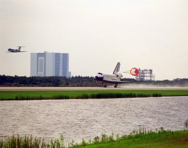 Framed by the Vehicle Assembly Building in the distance, at left, and the Mate-Demate Device, the Space Shuttle Atlantis with its drag chute deployed touches down on KSC?s Runway 33 at the conclusion of the STS-84 mission. The Shuttle Training Aircraft with astronaut Kenneth D. Cockrell at the controls is flying in front of Atlantis. Cockrell is acting deputy chief of the Astronaut Office. Main gear touchdown was at 9:27:44 EDT on May 24, 1997. The first landing opportunity was waved off because of low cloud cover. It was the 37th landing at KSC since the Shuttle program began in 1981, and the eighth consecutive landing at KSC. STS-84 was the sixth of nine planned dockings of the Space Shuttle with the Russian Space Station Mir. Atlantis was docked with the Mir for five days. STS-84 Mission Specialist C. Michael Foale replaced astronaut and Mir 23 crew member Jerry M. Linenger, who has been on the Russian space station since Jan. 15. Linenger returned to Earth on Atlantis with the rest of the STS-84 crew, Mission Commander Charles J. Precourt, Pilot Eileen Marie Collins, and Mission Specialists Carlos I. Noriega, Edward Tsang Lu, Elena V. Kondakova of the Russian Space Agency and Jean-Francois Clervoy of the European Space Agency. Foale is scheduled to remain on the Mir for approximately four months, until he is replaced by STS-86 crew member Wendy B. Lawrence in September. Besides the docking and crew exchange, STS-84 included the transfer of more than 7,300 pounds of water, logistics and science experiments and hardware to and from the Mir. Scientific experiments conducted during the STS-84 mission, and scheduled for Foale?s stay on the Mir, are in the fields of advanced technology, Earth sciences, fundamental biology, human life sciences, International Space Station risk mitigation, microgravity sciences and space sciences