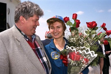 Veteran cosmonaut Valery Ryumin greets his wife, STS-84 Mission Specialist Elena V. Kondakova, with some flowers after the Space Shuttle orbiter Atlantis lands on KSC?s Runway 33. STS-84 was the sixth docking of the Space Shuttle with the Russian Space Station Mir. The nine-day STS-84 mission was Kondakova?s second space flight, but her first on the Space Shuttle. She spent 169 days in space as flight engineer of the 17th main mission on Mir from October 1994 to March 1995. Her husband is now director of the Mir-Shuttle program for Russia