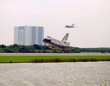 The Space Shuttle orbiter Atlantis rolls out on Runway 33 of KSC?s Shuttle Landing Facility at the conclusion of the nine-day STS-84 mission. The Shuttle Training Aircraft piloted by astronaut Kenneth D. Cockrell, acting deputy chief of the Astronaut Office, is flying above Atlantis. The Vehicle Assembly Building is at left. Main gear touchdown was at 9:27:44 EDT on May 24, 1997. The first landing opportunity was waved off because of low cloud cover. It was the 37th landing at KSC since the Shuttle program began in 1981, and the eighth consecutive landing at KSC. STS-84 was the sixth of nine planned dockings of the Space Shuttle with the Russian Space Station Mir. Atlantis was docked with the Mir for five days. STS-84 Mission Specialist C. Michael Foale replaced astronaut and Mir 23 crew member Jerry M. Linenger, who has been on the Russian space station since Jan. 15. Linenger returned to Earth on Atlantis with the rest of the STS-84 crew, Mission Commander Charles J. Precourt, Pilot Eileen Marie Collins, and Mission Specialists Carlos I. Noriega, Edward Tsang Lu, Elena V. Kondakova of the Russian Space Agency and JeanFrancois Clervoy of the European Space Agency. Foale is scheduled to remain on the Mir for approximately four months, until he is replaced by STS-86 crew member Wendy B. Lawrence in September. Besides the docking and crew exchange, STS-84 included the transfer of more than 7,300 pounds of water, logistics and science experiments and hardware to and from the Mir. Scientific experiments conducted during the STS-84 mission, and scheduled for Foale?s stay on the Mir, are in the fields of advanced technology, Earth sciences, fundamental biology, human life sciences, International Space Station risk mitigation, microgravity sciences and space sciences