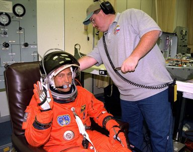 STS-84 Mission Specialist Carlos I. Noriega gets assistance from a suit technician as he dons his launch and entry suit during final prelaunch preparations in the Operations and Checkout Building. This will be Noriega?s first space flight. Noriega and six other crew members will depart shortly for Launch Pad 39A, where the Space Shuttle Atlantis awaits liftoff on a mission to dock with the Russian Space Station Mir