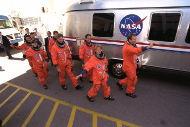 The STS-94 crew walks out of the Operations and Checkout Building and heads for the Astrovan that will transport them to Launch Pad 39A as KSC employees show their support. Waving to the crowd and leading the way are Mission Commander James D. Halsell, Jr. and Pilot Susan L. Still. Behind Still is Mission Specialist Donald A.Thomas, followed by Mission Specialist Michael L. Gernhardt , Payload Commander Janice Voss, and Payload Specialists Roger K.Crouch and Gregory T. Linteris. During the scheduled 16-day Microgravity Science Laboratory-1 (MSL-1) mission, the Spacelab module will be used to test some of the hardware, facilities and procedures that are planned for use on the International Space Station while the flight crew conducts combustion, protein crystal growth and materials processing experiments. Also onboard is the Hitchhiker Cryogenic Flexible Diode (CRYOFD) experiment payload, which is attached to the right side of Columbia?s payload bay.The Space Shuttle Columbia is scheduled to lift off when the launch window opens at 1:50 p.m. EDT, July 1. The launch window was opened 47 minutes early to improve the opportunity to lift off before Florida summer rain showers reached the space center