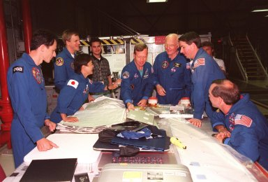 Around a table in Orbiter Processing Facility Bay 2 , STS-95 crew members look over equipment during the Crew Equipment Interface Test (CEIT) for their mission. From left, they are Mission Specialist Pedro Duque, of the European Space Agency; Payload Specialist Chiaki Mukai, of the National Space Development Agency of Japan (NASDA); Mission Specialist Scott E. Parazynski, M.D.; Pilot Steven W. Lindsey; Payload Specialist John H. Glenn Jr., senator from Ohio; Mission Specialist Stephen K. Robinson; and Mission Commander Curtis L. Brown Jr. Behind them is Adam Flagan, United Space Alliance-Houston. The CEIT gives astronauts an opportunity for a hands-on look at the payloads and equipment with which they will be working on orbit. The launch of the STS-95 mission, aboard Space Shuttle Discovery, is scheduled for Oct. 29, 1998. The mission includes research payloads such as the Spartan solar-observing deployable spacecraft, the Hubble Space Telescope Orbital Systems Test Platform, the International Extreme Ultraviolet Hitchhiker, as well as the SPACEHAB single module with experiments on space flight and the aging process