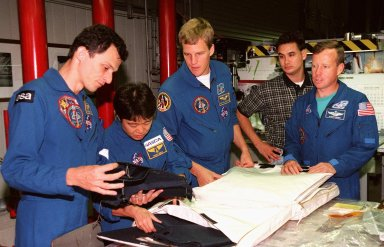 STS-95 crew members look over equipment in Orbiter Processing Facility Bay 2 during the Crew Equipment Interface Test (CEIT) for their mission. From left, they are Mission Specialist Pedro Duque, of the European Space Agency; Payload Specialist Chiaki Mukai, of the National Space Development Agency of Japan (NASDA); Mission Specialist Scott E. Parazynski; and Pilot Steven W. Lindsey. Behind them is Adam Flagan, United Space Alliance-Houston. The CEIT gives astronauts an opportunity for a hands-on look at the payloads and equipment with which they will be working on orbit. The launch of the STS-95 mission, aboard Space Shuttle Discovery, is scheduled for Oct. 29, 1998. The mission includes research payloads such as the Spartan solar-observing deployable spacecraft, the Hubble Space Telescope Orbital Systems Test Platform, the International Extreme Ultraviolet Hitchhiker, as well as the SPACEHAB single module with experiments on space flight and the aging process