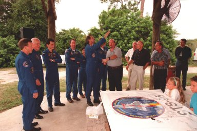 During a break in the Crew Equipment Interface Test (CEIT), the STS-95 crew gathers with United Space Alliance (USA) personnel and their families. From left are Pilot Steven W. Lindsey; Payload Specialist John H. Glenn Jr., a senator from Ohio; Pedro Duque, with the European Space Agency (ESA); Mission Specialist Stephen K. Robinson, Ph.D.; Chiaki Mukai, with the National Space Development Agency of Japan (NASDA); Mission Commander Curtis L. Brown Jr. (with arm raised); Mission Specialist Scott E. Parazynski, M.D.; Jim Furr, USA National Space Flight Awareness representative; Jack King, USA Public Affairs; Bob Sieck, KSC director of Shuttle Processing; and Ed Adamek, USA vice president and associate program manager for Ground Operations at KSC