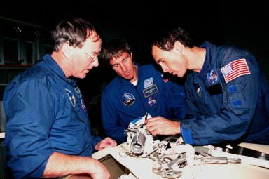 """KENNEDY SPACE CENTER, FLA. -- In the Orbiter Processing Facility Bay 1, STS-88 Mission Specialists (left to right) Jerry L. Ross; Sergei Krikalev, a cosmonaut from Russia; and James H. Newman examine equipment that will be on the Space Shuttle Endeavour during their upcoming flight. Launch of Mission STS-88 is targeted for Dec. 3, 1998. The STS-88 crew members are participating in a Crew Equipment Interface Test (CEIT), familiarizing themselves with the orbiter's midbody and crew compartments. Other crew members are Commander Robert D. Cabana, Pilot Frederick W. """"Rick"""" Sturckow and Mission Specialist Nancy J. Currie. STS-88 will be the first Space Shuttle launch for assembly of the International Space Station (ISS). The primary payload is the Unity connecting module which will be mated to the Russian-built Zarya control module, expected to be already on orbit after a November launch from Russia. The first major U.S.-built component of ISS, Unity will serve as a connecting passageway to living and working areas of the space station. Unity has two attached pressurized mating adapters (PMAs) and one stowage rack installed inside. PMA-1 provides the permanent connection point between Unity and Zarya; PMA-2 will serve as a Space Shuttle docking port. Zarya is a self-supporting active vehicle, providing propulsive control capability and power during the early assembly stages. It also has fuel storage capability"""