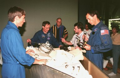 KENNEDY SPACE CENTER, FLA. -- Clad in their blue flight suits, STS-88 Mission Specialists (from left) Sergei Krikalev, a cosmonaut from Russia; Jerry L. Ross; and James H. Newman examine equipment from a toolbox that will be on the Space Shuttle Endeavour during their flight. Talking to Ross is Wayne Wedlake of United Space Alliance at Johnson Space Center, while Henry Thacker (facing camera), of Flight Crew Systems at KSC, looks on. Launch of mission STS-88 is targeted for Dec. 3, 1998. The STS-88 crew members are participating in a Crew Equipment Interface Test (CEIT) in the Orbiter Processing Facility Bay 1 to familiarize themselves with the orbiter's midbody and crew compartments. STS-88 will be the first Space Shuttle launch for assembly of the International Space Station (ISS). The primary payload is the Unity connecting module which will be mated to the Russian-built Zarya control module, expected to be already on orbit after a November launch from Russia. The first major U.S.-built component of ISS, Unity will serve as a connecting passageway to living and working areas of the space station. Unity has two attached pressurized mating adapters (PMAs) and one stowage rack installed inside. PMA-1 provides the permanent connection point between Unity and Zarya; PMA-2 will serve as a Space Shuttle docking port. Zarya is a self-supporting active vehicle, providing propulsive control capability and power during the early assembly stages. It also has fuel storage capability