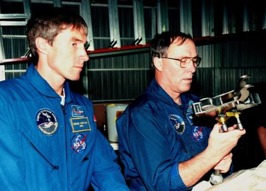"""KENNEDY SPACE CENTER, FLA. -- In the Orbiter Processing Facility Bay 1, STS-88 Mission Specialists Sergei Krikalev (left), a cosmonaut from Russia; and Jerry L. Ross examine equipment that will be aboard Space Shuttle Endeavour. Launch of mission STS-88 is targeted for Dec. 3, 1998. The STS-88 crew members are participating in a Crew Equipment Interface Test (CEIT), familiarizing themselves with the orbiter's midbody and crew compartments. Other crew members are Commander Robert D. Cabana, Pilot Frederick W. """"Rick"""" Sturckow and Mission Specialists Nancy J. Currie and James H. Newman. STS-88 will be the first Space Shuttle launch for assembly of the International Space Station (ISS). The primary payload is the Unity connecting module which will be mated to the Russian-built Zarya control module, expected to be already on orbit after a November launch from Russia. The first major U.S.-built component of ISS, Unity will serve as a connecting passageway to living and working areas of the space station. Unity has two attached pressurized mating adapters (PMAs) and one stowage rack installed inside. PMA-1 provides the permanent connection point between Unity and Zarya; PMA-2 will serve as a Space Shuttle docking port. Zarya is a self-supporting active vehicle, providing propulsive control capability and power during the early assembly stages. It also has fuel storage capability"""