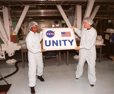 In the Space Station Processing Facility, holding the nameplate for the Unity connecting module are (left) Joan Higginbotham, with the Astronaut Office Computer Support Branch, and (right) Nancy Tolliver, with Boeing-Huntsville. Part of the International Space Station, Unity was expected to be transported to Launch Pad 39A on Oct. 26 for launch aboard Space Shuttle Endeavour on Mission STS-88 in December. The Unity is a connecting passageway to the living and working areas of ISS. While on orbit, the flight crew will deploy Unity from the payload bay and attach Unity to the Russian-built Zarya control module which will be in orbit at that time