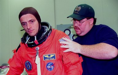 In the Operations and Checkout Building, STS-95 Mission Specialist Pedro Duque of Spain, with the European Space Agency, gets help with his suit from suit technician Tommy McDonald. The STS-95 crew were conducting flight crew equipment fit checks prior to launch on Oct. 29. STS-95 is expected to launch at 2 p.m. EST on Oct. 29, last 8 days, 21 hours and 49 minutes, and land at 11:49 a.m. EST on Nov. 7