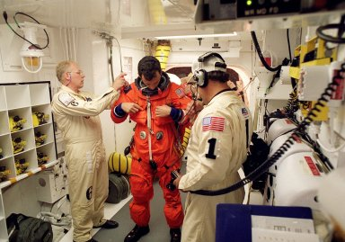 In the environmental chamber known as the white room, STS-95 Mission Specialist Pedro Duque of Spain, with the European Space Agency, is prepared by closeout room crew members Danny Wyatt (left) and Travis Thompson (right) for entry into the Space Shuttle Discovery for his first flight into space. The STS-95 mission, targeted for launch at 2 p.m. EST on Oct. 29, is expected to last 8 days, 21 hours and 49 minutes, and return to KSC at 11:49 a.m. EST on Nov. 7