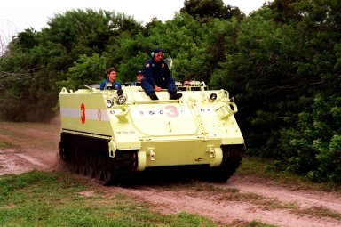 """STS-88 Mission Commander Robert D. Cabana operates an M-113, an armored personnel carrier, as part of emergency egress training under the watchful eye of instructor George Hoggard (left) during Terminal Countdown Demonstration Test (TCDT) activities. The TCDT also provides the crew with simulated countdown exercises and opportunities to inspect their mission payloads in the orbiter's payload bay. Mission STS-88 is targeted for launch on Dec. 3, 1998. It is the first U.S. flight for the assembly of the International Space Station and will carry the Unity connecting module. Others in the STS-88 crew are Pilot Frederick W. """"Rick"""" Sturckow and Mission Specialists Nancy J. Currie, Jerry L. Ross, James H. Newman, and Sergei Konstantinovich Krikalev, a Russian cosmonaut"""
