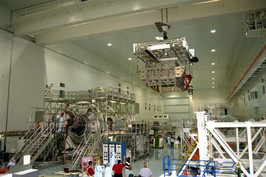 The Photovoltaic Module 1 Integrated Equipment Assembly (IEA) is moved past Node 1, seen at left, of the International Space Station (ISS) in Kennedy Space Center?s Space Station Processing Facility (SSPF). The IEA will be processed at the SSPF for flight on STS-97, scheduled for launch in April 1999. The IEA is one of four integral units designed to generate, distribute, and store power for the ISS. It will carry solar arrays, power storage batteries, power control units, and a thermal control system. The 16-foot-long, 16,850-pound unit is now undergoing preflight preparations in the SSPF