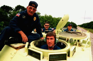 """STS-88 Mission Specialist Sergei Konstantinovich Krikalev (center front), a Russian cosmonaut, prepares to operate an M-113, an armored personnel carrier, as part of emergency egress training under the watchful eye of instructor George Hoggard (left) during Terminal Countdown Demonstration Test (TCDT) activities. The TCDT also provides the crew with simulated countdown exercises and opportunities to inspect their mission payloads in the orbiter's payload bay. Mission STS-88 is targeted for launch on Dec. 3, 1998. It is the first U.S. flight for the assembly of the International Space Station and will carry the Unity connecting module. Others in the STS-88 crew are Mission Commander Robert D. Cabana; Pilot Frederick W. """"Rick"""" Sturckow; and Mission Specialists Nancy J. Currie, Jerry L. Ross, and James H. Newman"""
