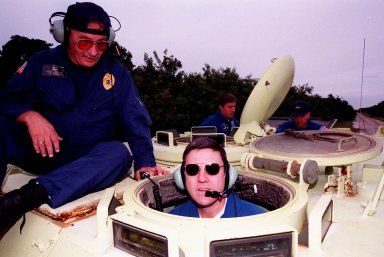 """STS-88 Mission Commander Robert D. Cabana (right) receives instruction on the operation of an M-113, an armored personnel carrier, as part of emergency egress training from George Hoggard during Terminal Countdown Demonstration Test (TCDT) activities. The TCDT also provides the crew with simulated countdown exercises and opportunities to inspect their mission payloads in the orbiter's payload bay. Mission STS-88 is targeted for launch on Dec. 3, 1998. It is the first U.S. flight for the assembly of the International Space Station and will carry the Unity connecting module. Others in the STS-88 crew are Pilot Frederick W. """"Rick"""" Sturckow and Mission Specialists Nancy J. Currie, Jerry L. Ross, James H. Newman, and Sergei Konstantinovich Krikalev, a Russian cosmonaut"""