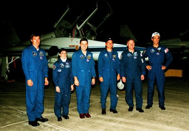 """The STS-88 crew members pose for a group photograph in front of a T-38 jet aircraft after their nighttime arrival at the Shuttle Landing Facility to take part in Terminal Countdown Demonstration Test (TCDT) activities. From left to right, they are Mission Specialist Sergei Krikalev, who is a Russian cosmonaut, Mission Specialist Nancy J. Currie, Mission Commander Robert D. Cabana, Pilot Frederick W. """"Rick"""" Sturckow, and Mission Specialists Jerry L. Ross and James H. Newman. The TCDT provides the crew with simulated countdown exercises, emergency egress training, and opportunities to inspect their mission payloads in the orbiter's payload bay. Mission STS-88 is targeted for launch on Dec. 3, 1998. It is the first U.S. flight for the assembly of the International Space Station and will carry the Unity connecting module. Ross and Newman will make three spacewalks to connect power, data and utility lines and install exterior equipment"""