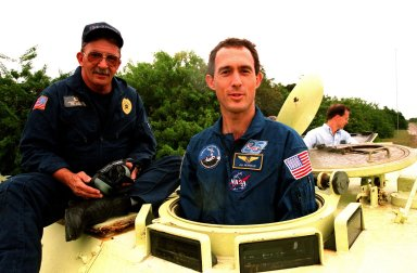 """STS-88 Mission Specialist James H. Newman (right) receives instruction on the operation of an M-113, an armored personnel carrier, as part of emergency egress training from George Hoggard during Terminal Countdown Demonstration Test (TCDT) activities. The TCDT also provides the crew with simulated countdown exercises and opportunities to inspect their mission payloads in the orbiter's payload bay. Mission STS-88 is targeted for launch on Dec. 3, 1998. It is the first U.S. flight for the assembly of the International Space Station and will carry the Unity connecting module. Others in the STS-88 crew are Mission Commander Robert D. Cabana; Pilot Frederick W. """"Rick"""" Sturckow; and Mission Specialists Nancy J. Currie, Jerry L. Ross, and Sergei Konstantinovich Krikalev, a Russian cosmonaut"""