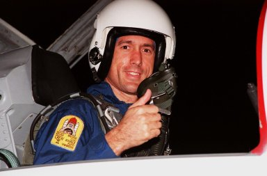 """STS-88 Mission Specialist James H. Newman gives a thumbs up on his nighttime arrival at the Shuttle Landing Facility in a T-38 jet aircraft to take part in Terminal Countdown Demonstration Test (TCDT) activities. The TCDT provides the crew with simulated countdown exercises, emergency egress training, and opportunities to inspect their mission payloads in the orbiter's payload bay. Mission STS-88 is targeted for launch on Dec. 3, 1998. It is the first U.S. flight for the assembly of the International Space Station and will carry the Unity connecting module. Others in the STS-88 crew are Mission Commander Robert D. Cabana, Pilot Frederick W. """"Rick"""" Sturckow, Mission Specialists Nancy J. Currie, Jerry L. Ross, and Sergei Krikalev, a Russian cosmonaut. Ross and Newman will make three spacewalks to connect power, data and utility lines and install exterior equipment"""