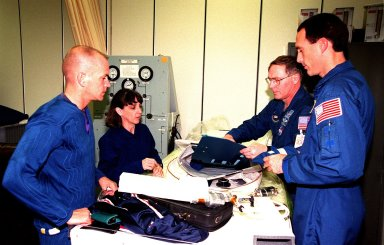 """(From left) STS-88 Pilot Frederick W. """"Rick"""" Sturckow and Mission Specialists Nancy J. Currie, Jerry L. Ross and James H. Newman examine some equipment that will be used on their upcoming space flight. The astronauts are in the Operations and Checkout Building as part of the Terminal Countdown Demonstration Test (TCDT) activities. Mission STS-88 is targeted for launch on Dec. 3, 1998. It is the first U.S. flight for the assembly of the International Space Station. The Space Shuttle Endeavour will carry the six-member crew and the Unity connecting module with its two attached pressurized mating adapters"""