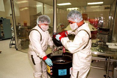KENNEDY SPACE CENTER, FLA. -- In the Spacecraft Assembly and Encapsulation Facility -2 (SAEF-2), Chris Voorhees and Satish Krishnan from the Jet Propulsion Laboratory remove a microprobe which will hitchhike on the Mars Polar Lander. Scheduled to be launched Jan. 3, 1999, aboard a Delta II rocket, the solar-powered spacecraft is designed to touch down on the Martian surface near the northern-most boundary of the south pole in order to study the water cycle there. The lander also will help scientists learn more about climate change and current resources on Mars, studying such things as frost, dust, water vapor and condensates in the Martian atmosphere. The Mars microprobes, called Deep Space 2, are part of NASA's New Millennium Program. They will complement the climate-related scientific focus of the lander by demonstrating an advanced, rugged microlaser system for detecting subsurface water. Such data on polar subsurface water, in the form of ice, should help put limits on scientific projections for the global abundance of water on Mars