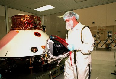 KENNEDY SPACE CENTER, FLA. -- In the Spacecraft Assembly and Encapsulation Facility -2 (SAEF-2), a JPL worker carries a Mars microprobe to the Mars Polar Lander at left. Two microprobes will hitchhike on the lander, scheduled to be launched Jan. 3, 1999, aboard a Delta II rocket. The solar-powered spacecraft is designed to touch down on the Martian surface near the northern-most boundary of the south pole in order to study the water cycle there. The lander also will help scientists learn more about climate change and current resources on Mars, studying such things as frost, dust, water vapor and condensates in the Martian atmosphere. The Mars microprobes, called Deep Space 2, are part of NASA's New Millennium Program. They will complement the climate-related scientific focus of the lander by demonstrating an advanced, rugged microlaser system for detecting subsurface water. Such data on polar subsurface water, in the form of ice, should help put limits on scientific projections for the global abundance of water on Mars