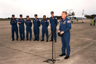 The STS-89 crew speak with the press after arriving at Kennedy Space Center's Shuttle Landing Facility in preparation for launch later this week. From left to right the crew include Commander Terrence Wilcutt; Pilot Joe Edwards Jr.; and Mission Specialists Bonnie Dunbar, Ph.D.; Salizhan Sharipov with the Russian Space Agency; Michael Anderson; James Reilly, Ph.D.; and Andrew Thomas, Ph.D. (at microphone). Dr. Thomas will succeed David Wolf, M.D., on the Russian Space Station Mir. Launch is scheduled for January 22 at 9:48 p.m. EST