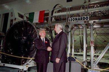 """KENNEDY SPACE CENTER, FLA. -- NASA Administrator Daniel S. Goldin (at right) shakes the hand of Sergio De Julio, president of the Italian Space Agency, Agenzia Spaziale Italiana (ASI), during the ceremony transferring the """"Leonardo"""" Multipurpose Logistics Module (MPLM) from ASI to NASA. The event was held in the Space Station Processing Facility beside Leonardo. The MPLM, a reusable logistics carrier, will be the primary delivery system used to resupply and return International Space Station cargo requiring a pressurized environment. Leonardo is the first of three MPLM carriers for the International Space Station. It is scheduled to be launched on Space Shuttle Mission STS-100, targeted for April 2000"""