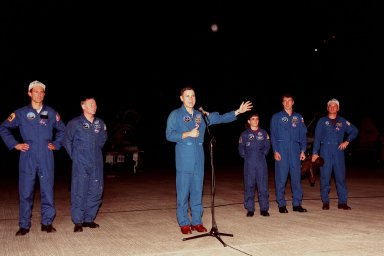 """Shortly after their arrival at the Shuttle Landing Facility, STS-88 crew members talk to the media. From left, they are Mission Specialists James H. Newman and Jerry L. Ross, Commander Robert D. Cabana (at microphone), Mission Specialists Nancy J. Currie and Sergei Konstantinovich Krikalev, and Pilot Frederick W. """"Rick"""" Sturckow. Krikalev is a Russian cosmonaut who has flown three times in space, once on the Space Shuttle and twice aboard the Russian Space Station Mir. The STS-88 mission is the fourth spaceflight for Cabana, sixth for Ross, third for Currie, third for Newman and first for Sturckow. The scheduled time of launch is 3:56 a.m. EST on Dec. 3 from Launch Pad 39A. The mission is the first U.S. launch for the International Space Station. Endeavour carries the Unity connecting module which the crew will be mating with the Russian-built Zarya control module already in orbit. In addition to Unity, Endeavour will carry two small replacement electronics boxes for possible repairs to Zarya batteries. The mission is scheduled to last nearly 12 days"""