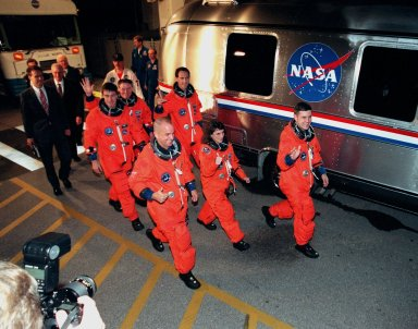 "STS-88 crew members depart the Operations and Checkout Building to board the astronaut van (at right) for the short journey to Launch Pad 39A where the Space Shuttle Endeavour is poised for liftoff of the first U.S. launch dedicated to the assembly of the International Space Station. In front row, from left, are Pilot Frederick W. ""Rick"" Sturckow, Mission Specialist Nancy J. Currie and Commander Robert D. Cabana. In back row, from left, are Mission Specialists Sergei Konstantinovich Krikalev, a Russian cosmonaut; Jerry L. Ross and James H. Newman. Liftoff is targeted for 3:35 a.m. EST on Dec. 4"