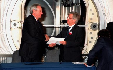 """KENNEDY SPACE CENTER, FLA. -- Sergio De Julio (at right), president of the Italian Space Agency, Agenzia Spaziale Italiana (ASI), shakes the hand of NASA Adminstrator Daniel S. Goldin while holding the document which signifies the transfer of the """"Leonardo"""" Multipurpose Logistics Module (MPLM) from ASI to NASA. The ceremonial event was held in the Space Station Processing Facility beside Leonardo. The MPLM, a reusable logistics carrier, will be the primary delivery system used to resupply and return International Space Station cargo requiring a pressurized environment. Leonardo is the first of three MPLM carriers for the International Space Station. It is scheduled to be launched on Space Shuttle Mission STS-100, targeted for April 2000"""