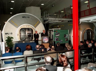 """NASA Administrator Daniel S. Goldin speaks at the Space Station Processing Facility ceremony transferring the """"Leonardo"""" Multipurpose Logistics Module (MPLM) from the Agenzia Spaziale Italiana (ASI) to NASA. Standing behind him in front of Leonardo is KSC Director Roy D. Bridges Jr. The MPLM, a reusable logistics carrier, will be the primary delivery system used to resupply and return International Space Station cargo requiring a pressurized environment. Leonardo is the first of three MPLM carriers for the International Space Station. It is scheduled to be launched on Space Shuttle Mission STS-100, targeted for April 2000"""