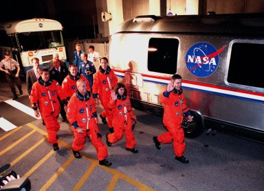 """After leaving the Operations and Checkout Building, the STS-88 crew approach the Astrovan for their trip to Launch Pad 39A. In the back row are (left to right) Mission Specialist Sergei Konstantinovich Krikalev, a Russian cosmonaut, and Mission Specialists Jerry L. Ross and James H. Newman. In the front row (left to right) are Pilot Frederick W. """"Rick"""" Sturckow, Mission Specialist Nancy J. Currie and Commander Robert D. Cabana. STS-88 is expected to launch at 3:56 a.m. EST with the six-member crew aboard Space Shuttle Endeavour on Dec. 3. Endeavour carries the Unity connecting module, which the crew will be mating with the Russian-built Zarya control module already in orbit. In addition to Unity, two small replacement electronics boxes are on board for possible repairs to Zarya batteries. The mission is expected to last 11 days, 19 hours and 49 minutes, with landing at 10:17 p.m. EST on Dec. 14"""