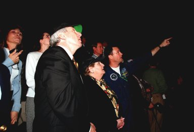 At the Banana Creek Viewing Site, NASA Administrator Daniel Goldin (left), U.S. Secretary of State Madeleine Albright (center) and astronaut Michael Lopez-Alegria watch the launch of STS-88 from Launch Pad 39A at 3:35:34 a.m. EST. STS-88 is the first U.S. mission dedicated to the assembly of the International Space Station (ISS). Lopez-Alegria is part of the STS-92 crew that is assigned to the fourth ISS assembly flight scheduled for launch on Oct. 28, 1999, aboard Discovery