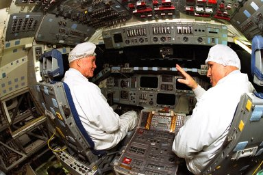 Ohio Senator John Glenn, at left, sits in the flight deck of the orbiter Columbia as astronaut Stephen Oswald explains some of the flight equipment to the senator at the Orbiter Processing Facility 3 at Kennedy Space Center. Senator Glenn arrived at KSC on Jan. 20 to tour KSC operational areas and to view the launch of STS-89 later this week. Glenn, who made history in 1962 as the first American to orbit the Earth, completing three orbits in a five-hour flight aboard Friendship 7, will fly his second space mission aboard Space Shuttle Discovery this October. Glenn is retiring from the Senate at the end of this year and will be a payload specialist aboard STS-95