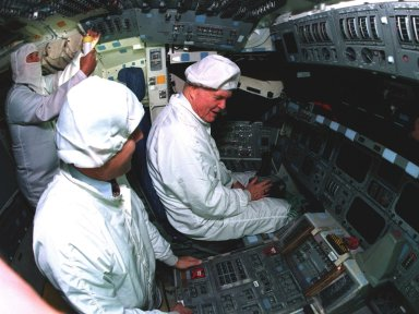 Ohio Senator John Glenn, at right, sits in the flight deck of the orbiter Columbia as astronaut Stephen Oswald listens to his questions regarding some of the flight equipment at the Orbiter Processing Facility 3 at Kennedy Space Center. Senator Glenn arrived at KSC on Jan. 20 to tour KSC operational areas and to view the launch of STS-89 later this week. Glenn, who made history in 1962 as the first American to orbit the Earth, completing three orbits in a five-hour flight aboard Friendship 7, will fly his second space mission aboard Space Shuttle Discovery this October. Glenn is retiring from the Senate at the end of this year and will be a payload specialist aboard STS-95
