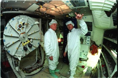 Astronaut Stephen Oswald, at right, explains Shuttle operations to Ohio Senator John Glenn on the orbiter Columbia's middeck at the Orbiter Processing Facility 3 at Kennedy Space Center. Senator Glenn arrived at KSC on Jan. 20 to tour KSC operational areas and to view the launch of STS-89 later this week. Glenn, who made history in 1962 as the first American to orbit the Earth, completing three orbits in a five-hour flight aboard Friendship 7, will fly his second space mission aboard Space Shuttle Discovery this October. Glenn is retiring from the Senate at the end of this year and will be a payload specialist aboard STS-95