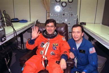 STS-89 Mission Specialist Salizhan Sharipov of the Russian Space Agency, at left, waves as he and his flight surgeon, Alexander Kulev, complete the donning of Sharipov?s launch/entry suit in the Operations and Checkout (O&C) Building. In 1994, Sharipov graduated from Moscow State University with a degree in cartography. He and six fellow crew members will soon depart the O&C and head for Launch Pad 39A, where the Space Shuttle Endeavour will lift off during a launch window that opens at 9:43 p.m. EST, Jan. 22. STS-89 is the eighth of nine planned missions to dock the Space Shuttle with Russia's Mir space station