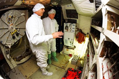 Astronaut Stephen Oswald, at left, explains Shuttle operations to Ohio Senator John Glenn on the orbiter Columbia's middeck at the Orbiter Processing Facility 3 at Kennedy Space Center. Senator Glenn arrived at KSC on Jan. 20 to tour KSC operational areas and to view the launch of STS-89 later this week. Glenn, who made history in 1962 as the first American to orbit the Earth, completing three orbits in a five-hour flight aboard Friendship 7, will fly his second space mission aboard Space Shuttle Discovery this October. Glenn is retiring from the Senate at the end of this year and will be a payload specialist aboard STS-95
