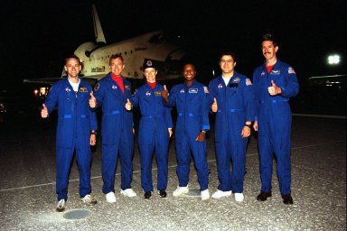 """KENNEDY SPACE CENTER, FLA. -- STS-89 crew members give a """"thumbs up"""" on KSC?s Runway 15 following completion of their successful mission that lasted nearly nine days. From left are Pilot Joe Edwards Jr.; Commander Terrence Wilcutt; and Mission Specialists Bonnie Dunbar, Ph.D.; Michael Anderson; Salizhan Sharipov of the Russian Space Agency; and James Reilly, Ph.D. Not shown are Mission Specialist Andrew Thomas, Ph.D., and returning astronaut and Mir 24 crew member David Wolf, M.D. STS-89 was the eighth docking of the Space Shuttle with the Russian Space Station Mir. Dr. Thomas succeeded Dr. Wolf on Mir, who has been on the Russian space station since late September. Dr. Thomas is scheduled to remain on Mir until the STS-91 Shuttle mission returns in June 1998. In addition to the docking and crew exchange, STS-89 included the transfer of science, logistical equipment and supplies between the two orbiting spacecrafts"""
