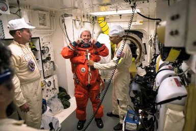 STS-89 Mission Specialist Andrew Thomas, Ph.D., is assisted with his ascent and re-entry flight suit in the white room at Launch Pad 39A before entering Space Shuttle Endeavour for launch. The STS-89 mission will be the eighth docking of the Space Shuttle with the Russian Space Station Mir. After docking, Thomas will transfer to the space station, succeeding David Wolf, M.D., who will return to Earth aboard Endeavour. Dr. Thomas will live and work on Mir until June. STS-89 is scheduled for a Jan. 22 liftoff at 9:48 p.m