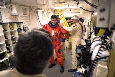 STS-89 Mission Specialist Salizhan Sharipov of the Russian Space Agency is assisted with his ascent and re-entry flight suit in the white room at Launch Pad 39A before entering Space Shuttle Endeavour for launch. The STS-89 mission will be the eighth docking of the Space Shuttle with the Russian Space Station Mir. After docking, Mission Specialist Andrew Thomas, Ph.D., will transfer to the space station, succeeding David Wolf, M.D., who will return to Earth aboard Endeavour. Dr. Thomas will live and work on Mir until June. STS-89 is scheduled for a Jan. 22 liftoff at 9:48 p.m